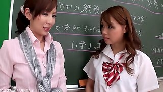 Seductive Asian lesbians kissing each other passionately in class